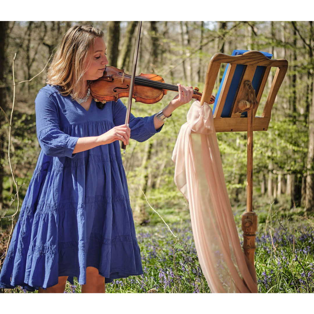 Violinist playing in bluebell wood