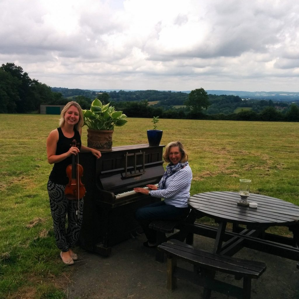 Jennifer and Diane posed at an upright piano, in a field!